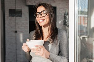 Beautiful lady wearing eyeglasses drinking coffee
