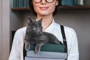 Vertical image of Authoress holding books with cat on them