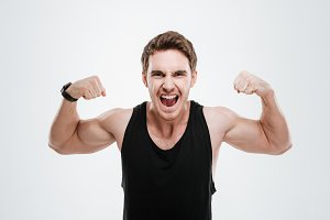 Smiling young man showing his biceps.
