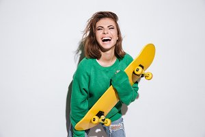 Pretty skater lady holding skateboard.