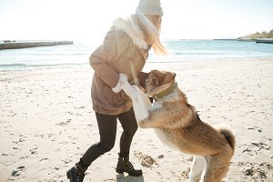 Playful young lady walks in winter beach with dog