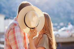 Couple Kissing Behind Hat