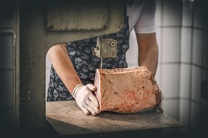 Male butcher's hand slicing meat