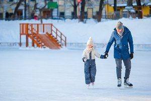 Little adorable girl with father learning to skate on ice-rink