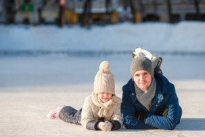 Portrait of little adorable girl and young father skating