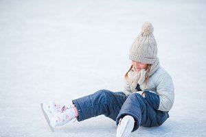 Little adorable girl lying on ice with skates after fall