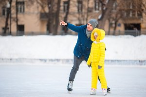 Little girl learning to skate with her father on ice-rink outdoors