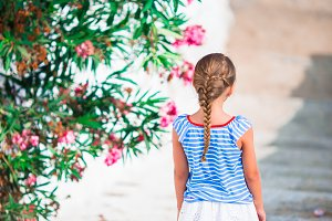Beautiful girl at street of typical greek traditional village on Mykonos Island, in Greece