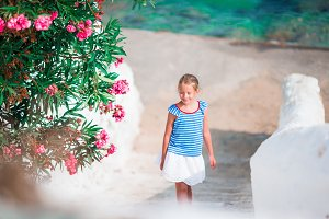 Kid at street of typical greek traditional village with white walls and colorful doors on Mykonos Island, in Greece
