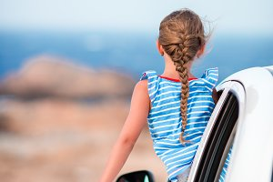 Little girl on vacation traveling by car background beautiful view of sea