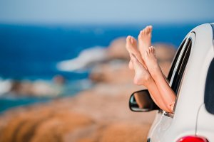 Closeup of family feet showing from car window background beautiful landscape