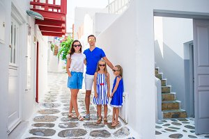 Family vacation in Europe. Parents and kids at street of typical greek traditional village on Mykonos Island, in Greece