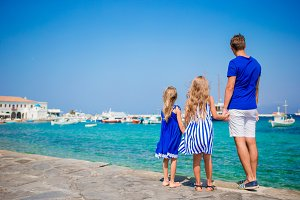Family vacation in Europe. Father and kids background Mykonos town in Greece