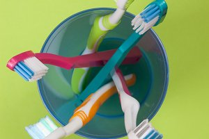 Toothbrushes in a blue plastic glass on a green background