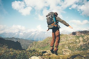 Man jumping with backpack mountains