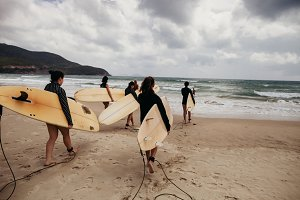 women surfers with surfing boards