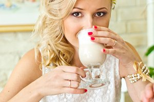 Blonde drinks latte in cosy cafe