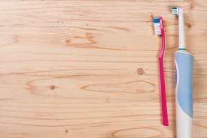 electric and manual toothbrushes on the light wooden background with copy space for your text. Top view