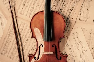 Violin lying on the old music notes