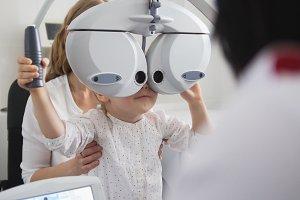 Children ophthalmology - optometrist Checks Eye of little girl