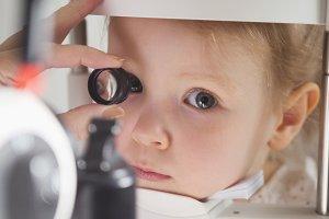 Child's ophthalmology - doctor optometrist checks eyesight for little girl