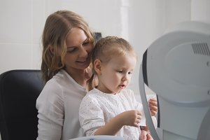 Optometrist checks child's eyesight - mother and child in ophthalmologist room