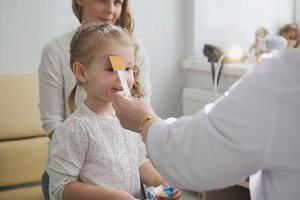 Cute blonde girl with mommy in child's ophthalmology - optometrist diagnosis eyesight