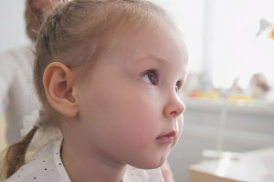 Portrait of little adorable blonde girl in child's ophthalmology clinic