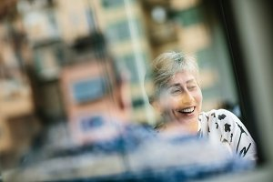 Laughing mature lady through glass