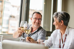 Mature laughing couple clinking glasses