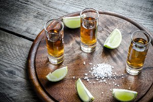 Glasses of tequila on wooden board