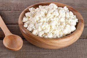 Cottage cheese in a wooden bowl on old wooden background