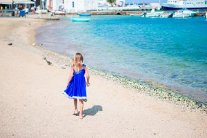 Back view of adorable little girl on beach vacation