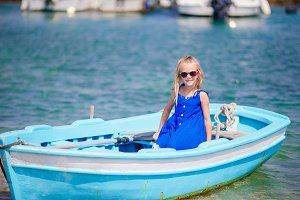 Little girl in blue boat in the sea bay in Greece. Little kid enjoy swimming in the small boat.