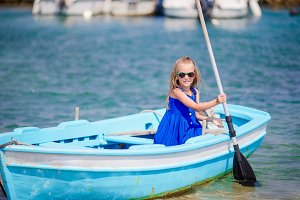 Cute girl in blue boat in the sea bay near the town of Mykonos in Greece. Little kid enjoy swimming in the small boat.