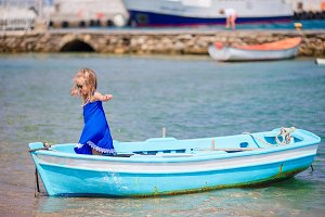 Little girl in blue boat in the sea bay near Mykonos in Greece. Little kid enjoy swimming in the small boat.