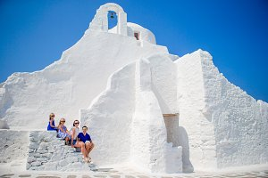 Family of four on the stairs of Paraportiani church on Mykonos Island, in Greece