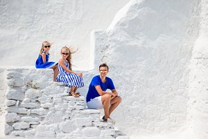 Family of three on the stairs of Paraportiani church on Mykonos Island, in Greece