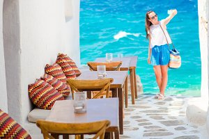 Beautiful sea view in outdoor cafe Mykonos on Cyclades islands. Young woman taking selfie with this amazing view