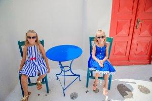Two girls in blue dresses sitting in outdoor cafe on street of typical greek village on Mykonos Island, Greece