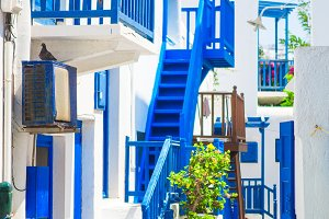 Traditional houses with blue doors and windows in the narrow streets of greek village