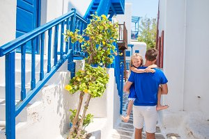 Family outdoor in the greek beautiful street in Cyclades isand