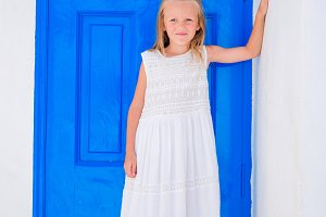 Adorable little girl at street of typical greek village background blue doors in Greece