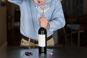 Senior man opening wine bottle with blank label