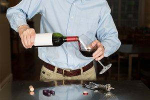 Senior man pouring from wine bottle with blank label