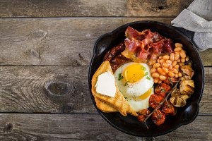 Full english breakfast - eggs, bacon, beans, toast, coffee and juice