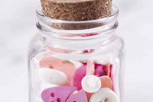 A jar full of pink buttons, white background