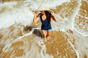 girl in vietnamese hat on beach