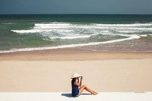 woman in vietnamese hat on beach