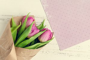 Pink tulips on white shabby chic background